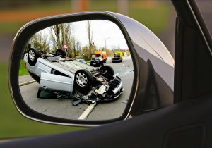 Flipped over vehicle in the mirror of car