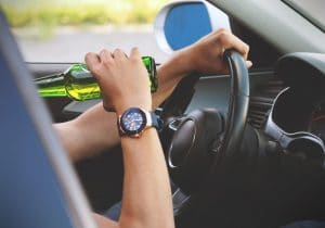 person with watch drinking beer while driving
