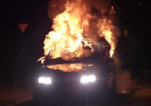 A car in flames during the night time