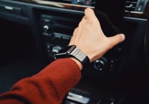 person with watch grabbing cell phone in a car
